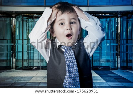 Fun, child dressed businessman with hands in his tie and skyscrapers in the background - stock photo