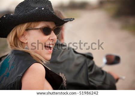 Fun couple riding on a motorcycle outside