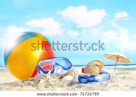 Fun day at the beach with goggles and beach ball - stock photo