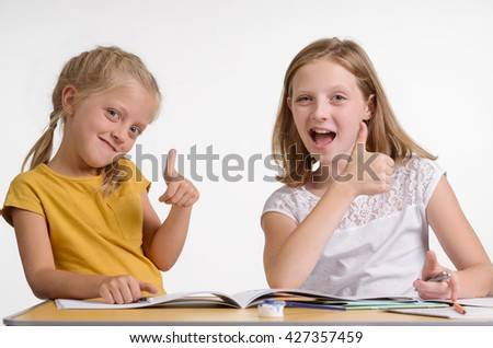 Fun during homework is the best way to combine leisure and education. Children who love to learn new things. Two adorable sisters in the classroom show that everything is OK and smile. - stock photo