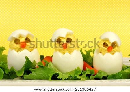 Fun Easter breakfast of hatching chicks made of boiled eggs with yellow background                     - stock photo