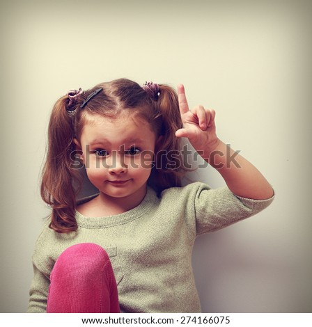 Fun emotion kid girl with good idea showing finger up on empty copy space. Closeup vintage color portrait - stock photo