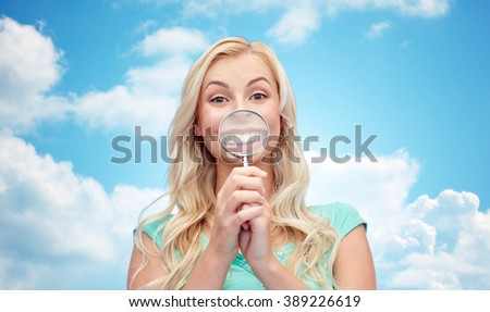 fun, emotions, expressions and people concept - happy smiling young woman or teenage girl having fun with magnifying glass over blue sky and clouds background - stock photo