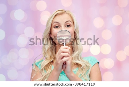 fun, emotions, expressions and people concept - happy smiling young woman or teenage girl having fun with magnifying glass over pink holidays lights background - stock photo
