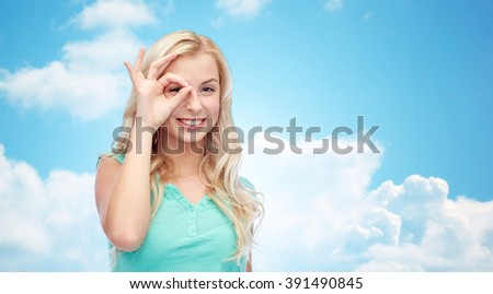 fun, emotions, expressions and people concept - smiling young woman or teenage girl making ok hand gesture over blue sky and clouds background - stock photo