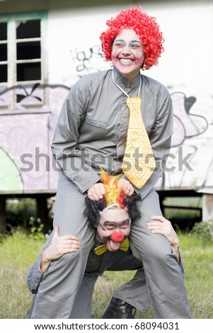 Fun Excitement And Amusement Is In The Expression Of A Laughing Carnival Clown Traversing On Another Clowns Back In A Playful Carnival Ride - stock photo