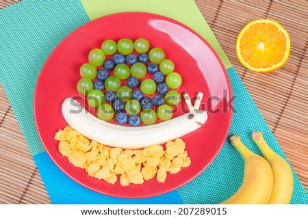 Fun food. Snail made from fruits - stock photo