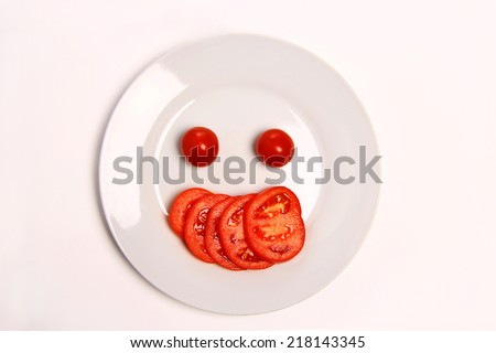 Fun food  - tomatoes  making smiley face served on a white plate on white background.