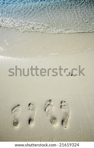 Fun footsteps on the coral sandy beach - stock photo