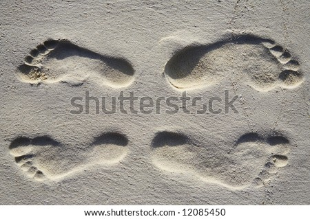 Fun four footsteps on a coral sandy beach
