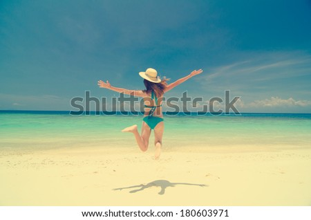 fun girl jumping holiday on a beach retro vintage effect - stock photo
