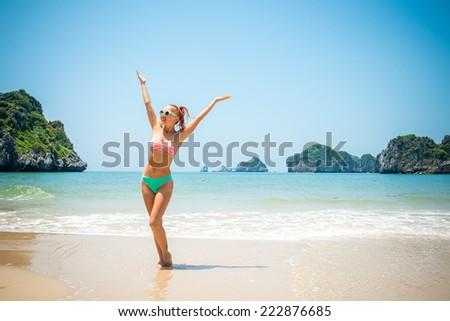 Fun girl wearing bikini having good time on a beach - stock photo
