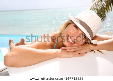 Fun girl with hat suntanning by the pool