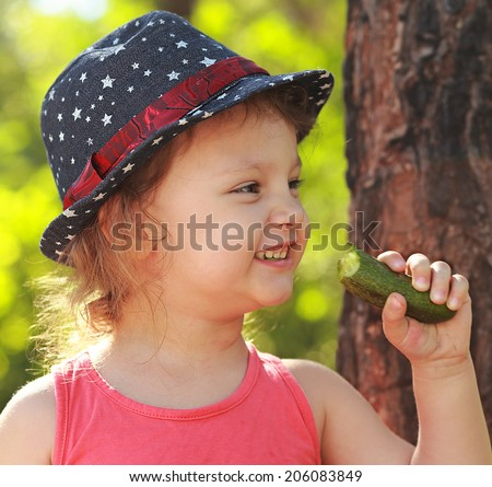 Fun happy eating cucumber and smiling on park green background. Closeup portrait - stock photo