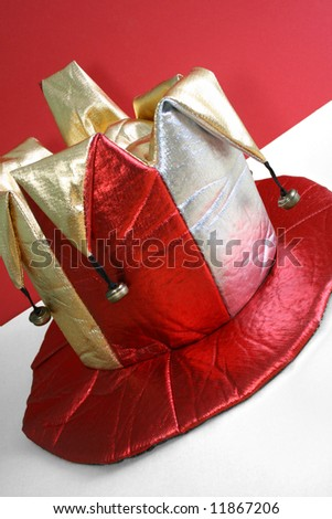 fun hat worn by a jester against the red background - stock photo