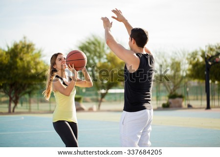 Fun Hispanic couple playing basketball against each other and having lots of fun - stock photo
