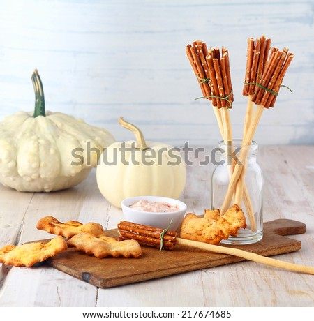 Fun homemade rustic Halloween witches broomstick appetizers made from bread sticks and pretzels served on a wooden board with a savory dip and bat biscuits - stock photo