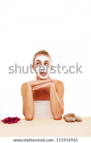 Fun image of a bored woman in a face mask sitting at a table in a spa wondering when it will be removed by the beautician - stock photo