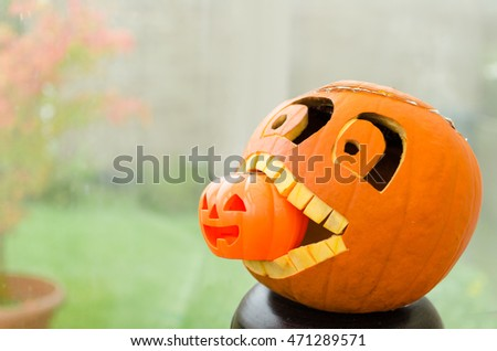 Fun image of a Halloween pumpkin carved into shape of a face eating a smaller version of itself. Hallow's Eve celebration concept. Autumn wallpaper. Fall background.
