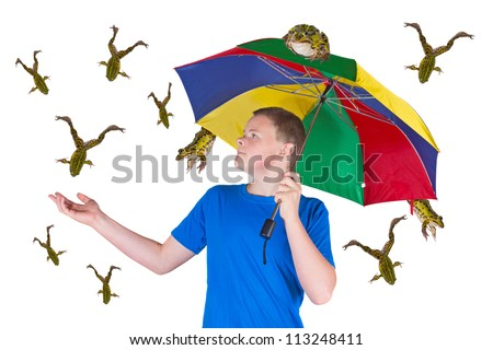 Fun image of an attractive young man sheltering under a colourful umbrella holding out his hand in surprise because it is raining frogs instead of raindrops isolated on white
