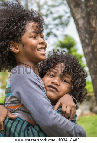 Fun in the park. Portrait of two little brother boy hugging having a good happy time in the park. Education green environment spring and summer time love family back to school concept