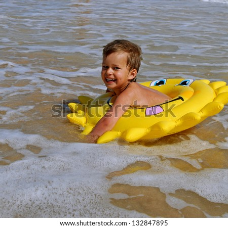 Fun in the sea. Little girl is swimming with bright  floatie.