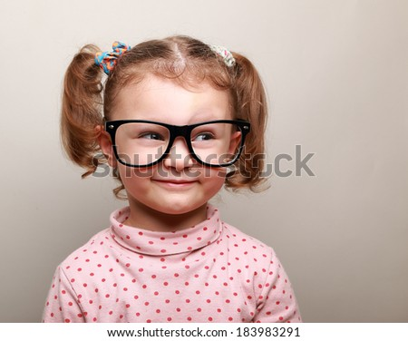 Fun kid girl in glasses looking on empty copy space - stock photo
