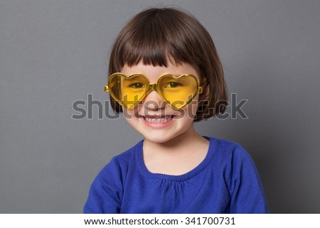fun kid glasses concept - ecstatic preschool child wearing yellow heart-shape glasses for comic disco outfit or positive future,studio shot - stock photo