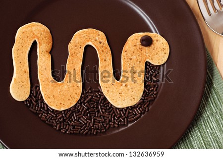 Fun kid's breakfast of a snake pancake with a chocolate chip for the eye and sprinkles added as decoration for the ground. - stock photo