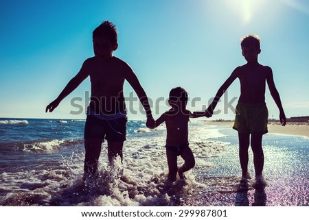 Fun kids playing splash at beach - stock photo