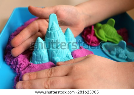 Fun kinetic sand. Happy child with built sandcastle - stock photo