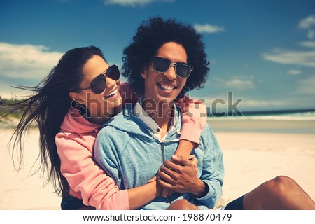 Fun Latino couple at the beach embracing and in love smiling - stock photo