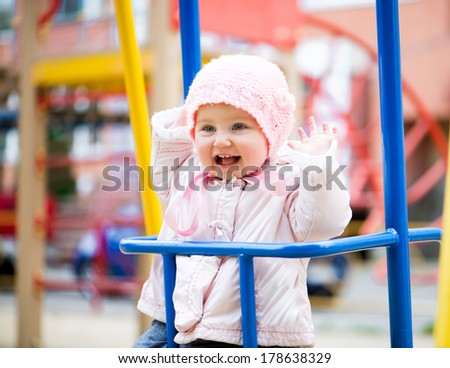 fun little baby swinging at the park - stock photo