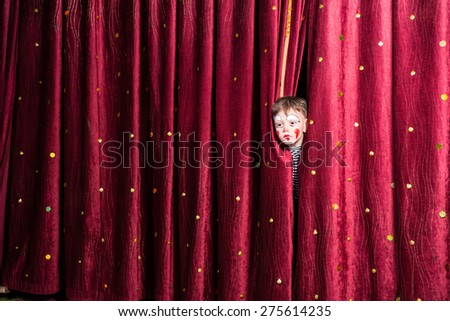 Fun little boy in makeup waiting for his acting cue poking his head out between the curtains as he waits to make his entrance on stage during the performance - stock photo
