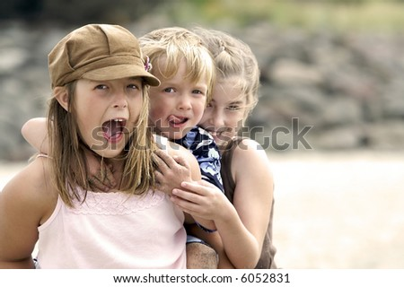 Fun loving cousins playing at the beach - stock photo