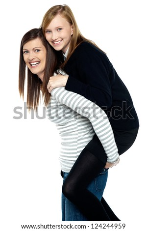 Fun loving duo of mother and daughter. Piggy ride fun. - stock photo