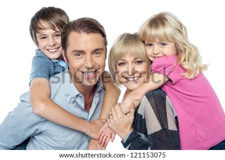 Fun loving family of four. Kids enjoying piggy ride. Indoor studio shot. - stock photo