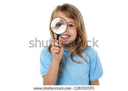 Fun loving girl child holding magnifying glass in front of her eye.