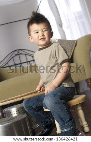 Fun loving young child hold drum sticks and plays kitchen utensils - stock photo