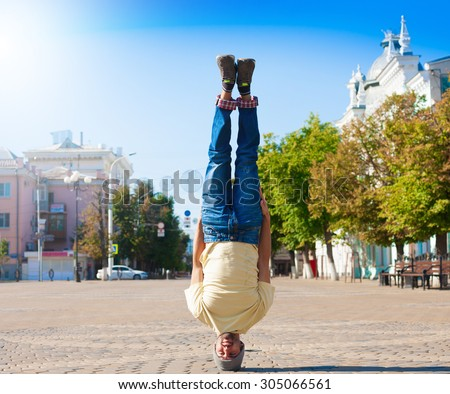 Fun man dancing. Has yellow t-shirt, blue jeans, gray shoes sneakers, slim sport body. Motion on great urban city. Amazing portrait. Sports acrobatic handstand. Fitness concept. Cool jump. Creative - stock photo