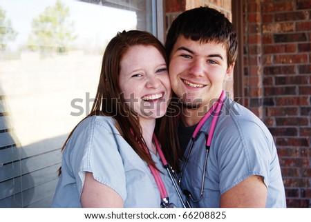 Fun nurses playing man and woman - stock photo