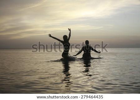 fun on the beach , girls in bikini playing in water, girls in swimsuit jumping out of water on sandy beach fashion photo of sensual beautiful girls playing in water on summer beach in sunlight rays - stock photo