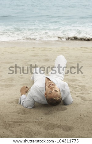 Fun outdoor portrait of a young smiling man on the beach looking back - stock photo