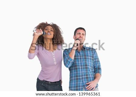 Fun pair singing at karaoke on white background - stock photo