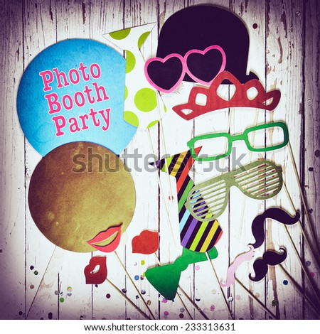 Fun photo booth party background with colorful paper fashion accessories, lips, moustaches and balloons with text - Photo Booth Party - surrounded by a vignette, square format - stock photo