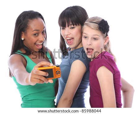 Fun photography with digital camera for three pretty young teenager girl friends a blonde caucasian, an oriental Japanese and an African American mixed race student all having a laugh together. - stock photo