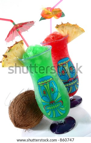 Fun plastic tiki glasses filled with colorful icy drinks and a coconut isolated on a white background. - stock photo