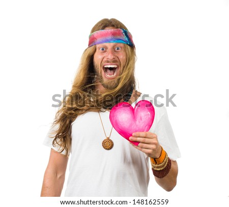 Fun portrait of a very happy hippie man holding a love heart and shouting - stock photo