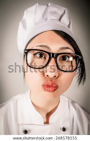Fun portrait of a young female Asian chef wearing glasses and a toque making a kissing gesture puckering up her lips and leaning towards the camera