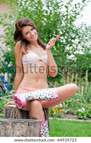 Fun portrait of a young model in bikini with a lollipop